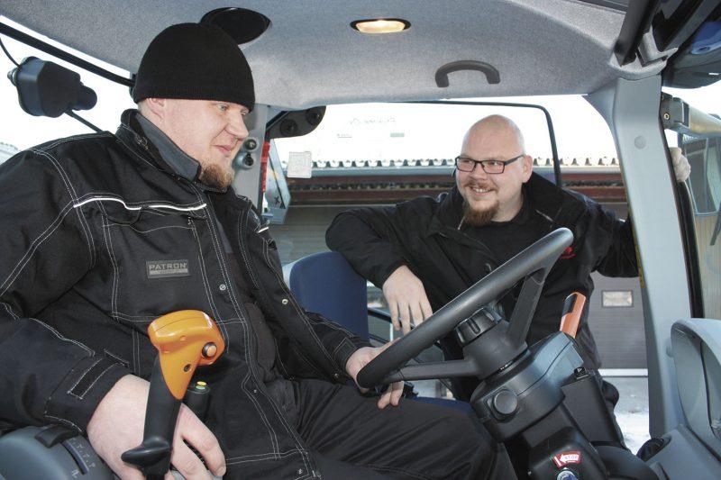 Hymy herkässä. Uuden traktorin luovutushuollon juuri tehnyt mekaanikko Jussi Väisänen (vas.) kertaa tärkeimmät asiat konemyyjä Eero Immosen kanssa.